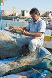 修理捕鱼网的渔夫 免版税库存照片
