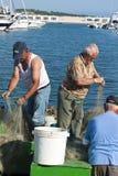 修理捕鱼网的渔夫 免版税库存图片