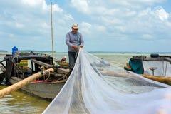修理捕鱼网的菲什曼 免版税图库摄影