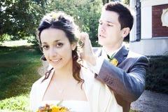 修理新郎头发的新娘 库存图片