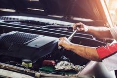 修理有板钳的技工一辆汽车在修理公司 图库摄影