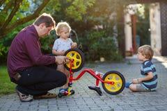 修理有父亲ou的两个逗人喜爱的男孩画象自行车车轮 免版税图库摄影