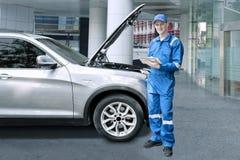 修理有片剂的欧洲技工一辆汽车 库存图片