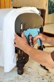 修理有订书机的室内装饰工一把扶手椅子 免版税库存图片