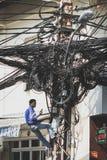 修理杂乱缆绳-通讯网络的电工 库存照片