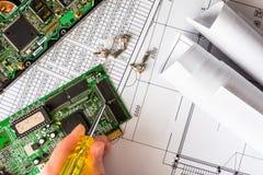 修理残破的计算机,拿着螺丝刀的手 免版税库存照片