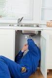 修理水槽的管道工的纵向 免版税图库摄影