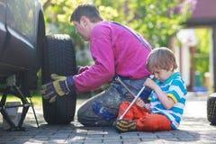 修理汽车和变速轮的父亲和可爱的小男孩 免版税库存图片