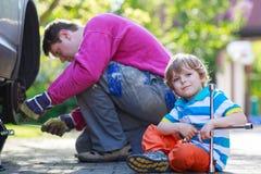 修理汽车和变速轮的父亲和可爱的小男孩 图库摄影