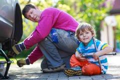 修理汽车和变速轮的父亲和可爱的小男孩 免版税库存照片