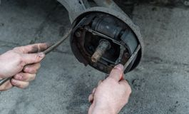 修理汽车和检查的人刹车鼓制动块使用两把螺丝刀 免版税库存图片