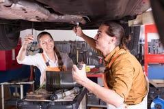 修理汽车的两位技工 免版税库存照片