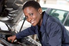 修理汽车的少妇技工 免版税库存照片