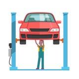 修理汽车的技工在自动卷扬机举了 免版税图库摄影