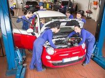 修理在车库的广泛汽车机械师一辆汽车 免版税库存照片
