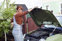 修理汽车的美丽的女孩 免版税图库摄影
