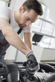 修理汽车的年轻维护工程师在汽车商店 免版税库存图片
