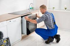 修理烤箱的安装工 免版税库存图片