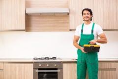 修理烤箱的年轻承包商在厨房里 库存图片
