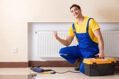 修理热化盘区的年轻安装工承包商 免版税图库摄影