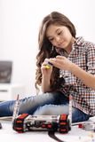 修理电子玩具的高兴女孩在机器人学实验室 免版税库存图片
