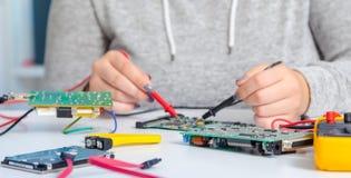 修理电子电路板的女小学生 适配器计算机图表查出的维修服务螺丝刀白色 免版税图库摄影