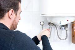 修理电水加热器的水管工 库存图片