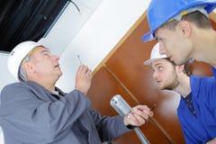 修理空调的电工安装工和学徒在房子里 免版税图库摄影
