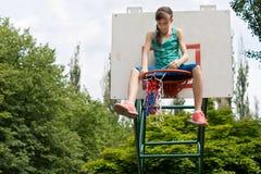 修理篮球网的十几岁的女孩 库存图片
