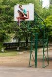 修理篮球网的年轻十几岁的女孩 免版税图库摄影