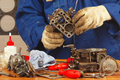 修理老发动机气化器的技工 免版税库存照片