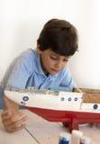 修理老木船的男孩 免版税库存照片