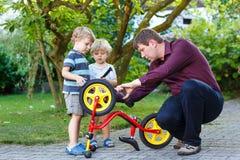 年轻修理自行车的人和两个小儿子户外。 免版税库存照片