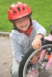 修理自行车的小女孩 库存图片
