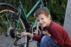 修理自行车的小男孩 免版税库存照片
