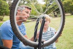 修理自行车的父亲和他的儿子 库存图片