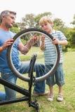 修理自行车的父亲和他的儿子 免版税库存照片