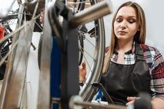 修理自行车的轮子的殷勤技术员 免版税库存照片