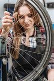 修理自行车的轮子的年轻技术员 库存图片