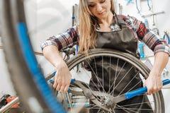 修理自行车的链子的女性运动工作者 库存图片