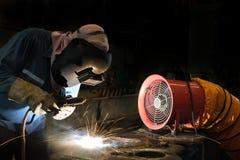 修理表面的焊工由盾金属电弧焊接 库存照片