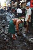 修理路的工作者在缅甸的暴雨以后 免版税库存照片