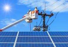 修理输电线的导线的在桶水力举的平台的电工有在太阳能驻地的photovoltaics的 免版税库存照片