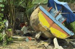 修理那条残破的小船 免版税库存照片