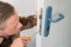 修理门锁的木匠 免版税库存照片
