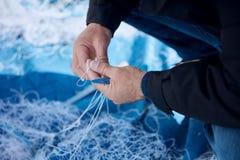 修理鱼网的渔夫 免版税图库摄影