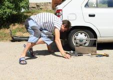 修理年轻人的残破的汽车人 库存图片