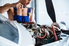 修理整体定象引擎的人在飞机上 免版税库存图片