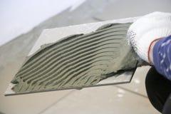 修理-室内装璜 放置地板陶瓷砖 人` s手套的手铺磁砖工与小铲涂了水泥灰浆  库存照片