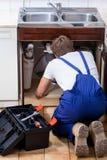 修理水槽的安装工 免版税库存照片